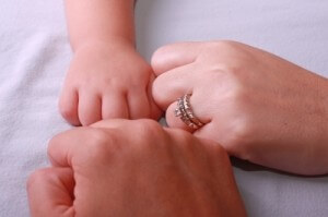 Couple with new baby's hands in a circle