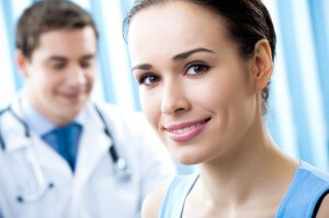 Happy female patient and doctor at office