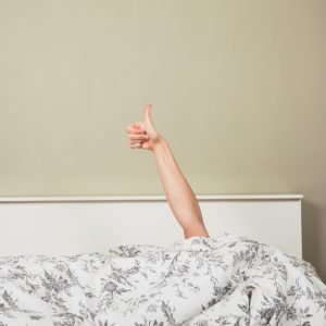 menopausal woman giving thumbs up in bed