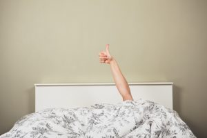 woman giving thumbs up in bed
